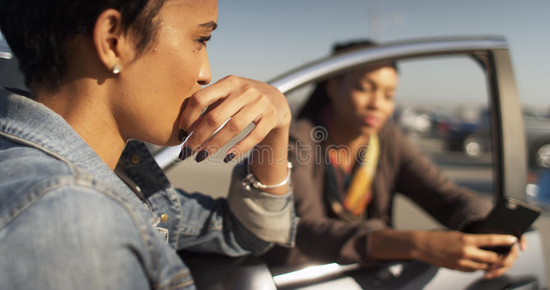 Two black women friends leaning against car talking and texting. On smart phone royalty free stock image