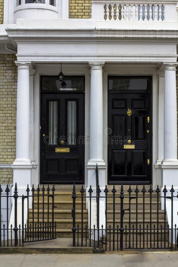 Two black Wooden Doors to residential building in London. Typical door in the English style royalty free stock photo