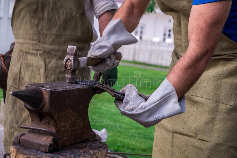Two blacksmiths near the anvil. One hacks a horseshoe with a ham stock photo