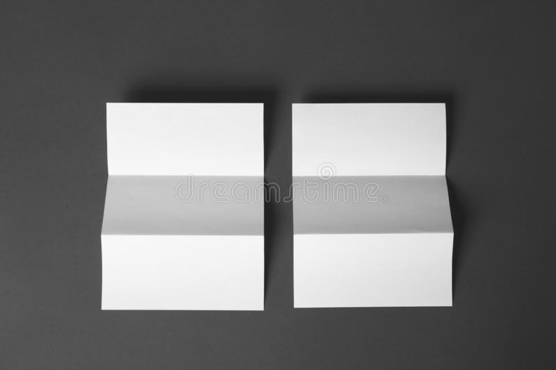 Two blank brochures on dark grey background. Mock up for design. Two blank brochures on dark grey background, flat lay. Mock up for design stock image