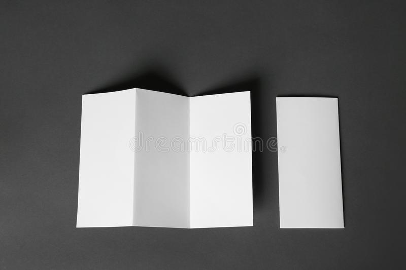 Two blank brochures on dark grey background. Mock up for design. Two blank brochures on dark grey background, flat lay. Mock up for design royalty free stock images