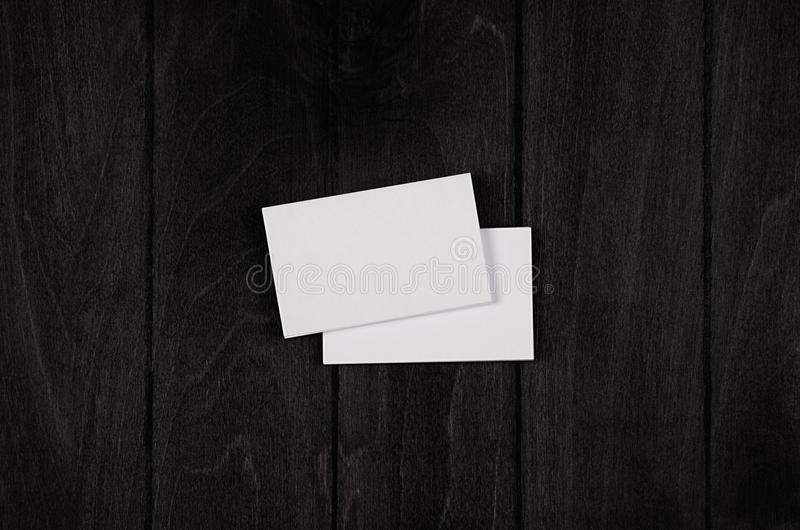 Two blank corporate identity business cards on black stylish wood background, top view, template. Two blank corporate identity business cards on black stylish royalty free stock image