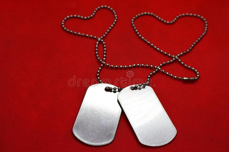 Two blank dog tags on red background stock photography