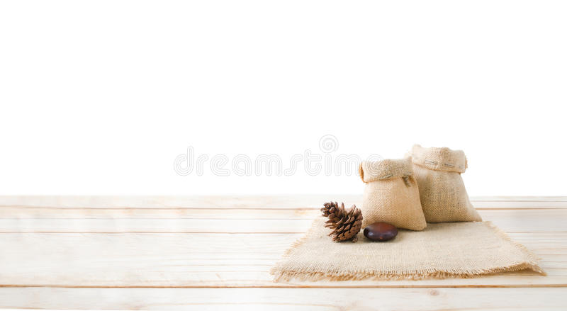 Two of blank hemp sack bag and pine cones on wood table top floor isolated on white background with clipping path royalty free stock photos