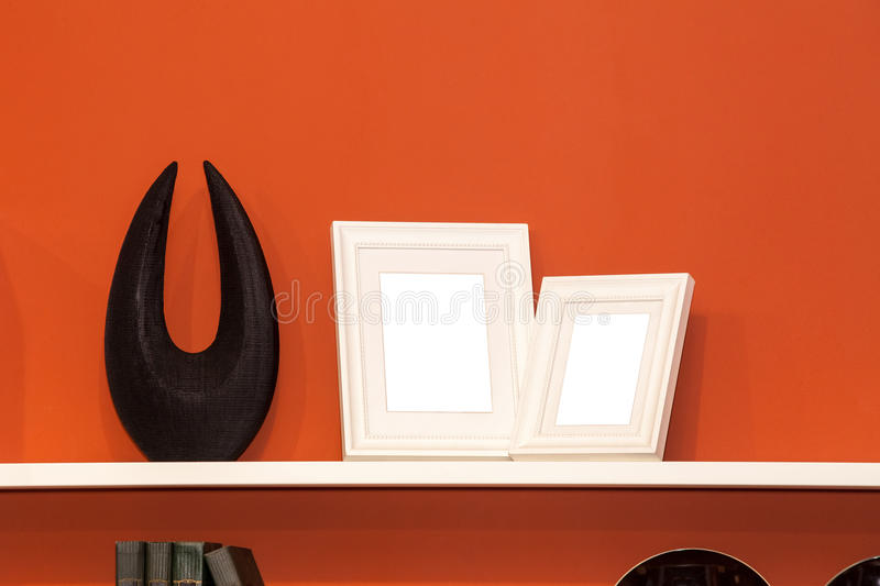 Two blank photo frames on the bookshelf stock images