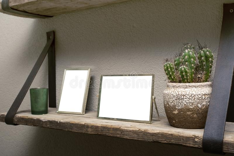 Two blank picture frames and cactus decoration on wooden shelf, industrial retro interior design stock photo