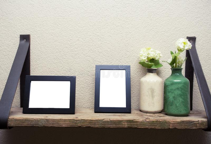 Two blank picture frames with decoration flowers on wood shelf industrial design royalty free stock images
