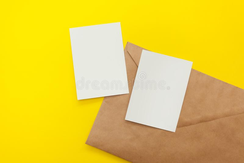 Two blank postcard with brown envelope on yellow background royalty free stock photos