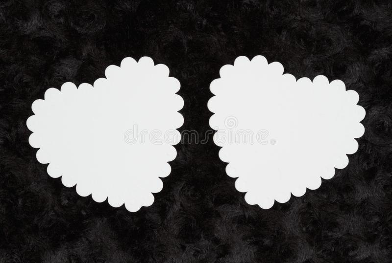 Two blank white hearts on black rose textured plush fabric stock photos