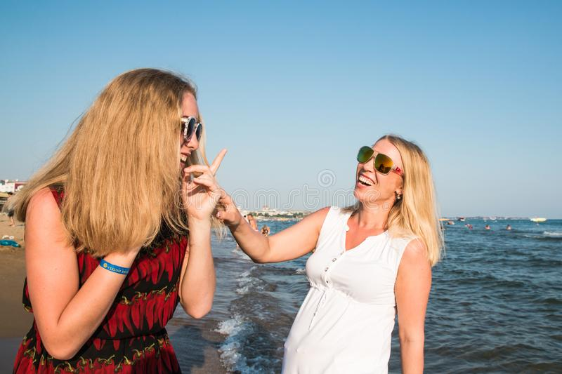 Two blond girls on the beach near sea. Or ocean. Mother and daughter have fun together stock photos