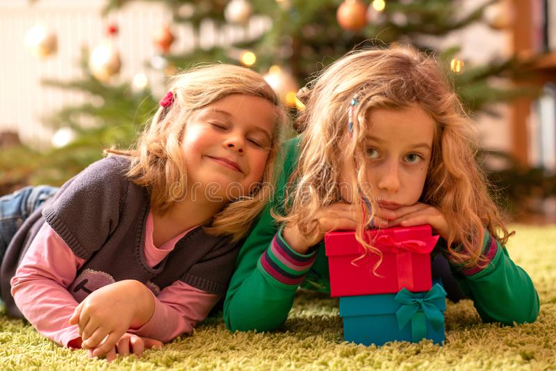 Two girls with presents in front of christmas tree royalty free stock image