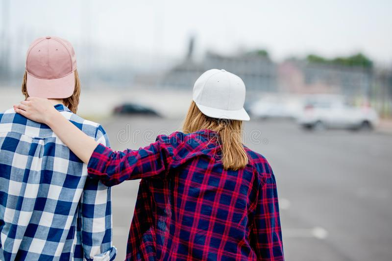 Two blond girls wearing checkered shirts, caps and denim shorts are standing with their backs on the empty car park stock images