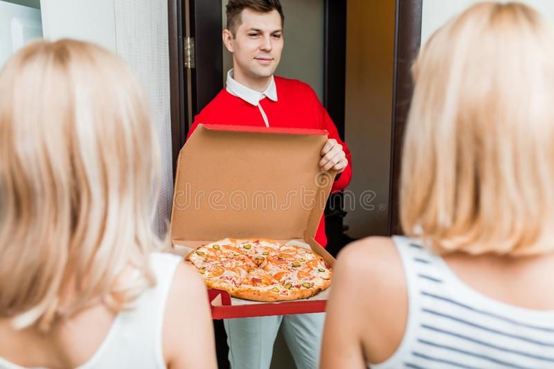 Two young caucasian woman receiving pizza from delivery man at home. Two blonde caucasian girl ordered the delivery of pizza at home. Cropped shot of delivery royalty free stock photos