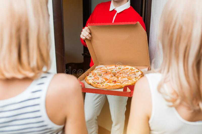Two young caucasian woman receiving pizza from delivery man at home. Two blonde caucasian girl ordered the delivery of pizza at home. Cropped shot of delivery royalty free stock photo