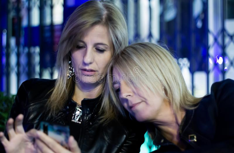 Two blonde friendly women watching a message together in the smartphone royalty free stock photo