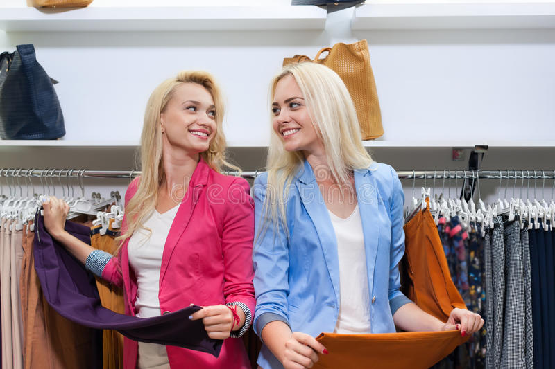 Two Blonde Woman Shopping Buying Fitting Pants, Happy Smiling Girls Customers Fashion Shop Choosing Clothes. In Retail Store royalty free stock photography