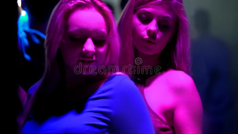 Two blonde women enjoying dance in night club, young people relaxing at disco stock photography
