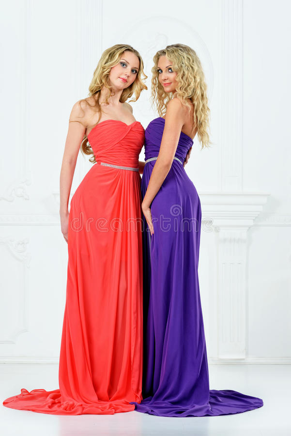 Two blonde women in evening dresses. Two beautiful blonde women in very long evening dresses stock photo