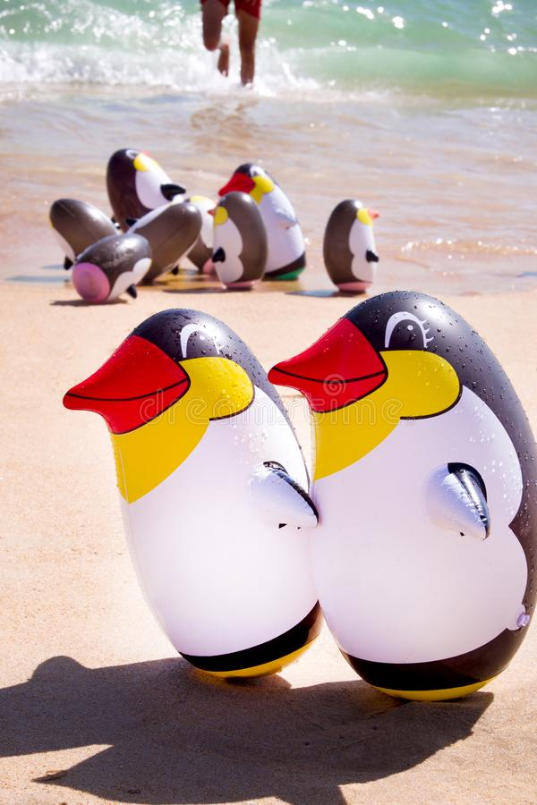 Two blow up penguins on a sandy beach with a group blow up peguins behind royalty free stock photos