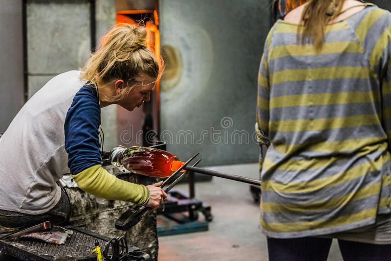 Two Blowing Glass Artists Finishing a Piece. stock images