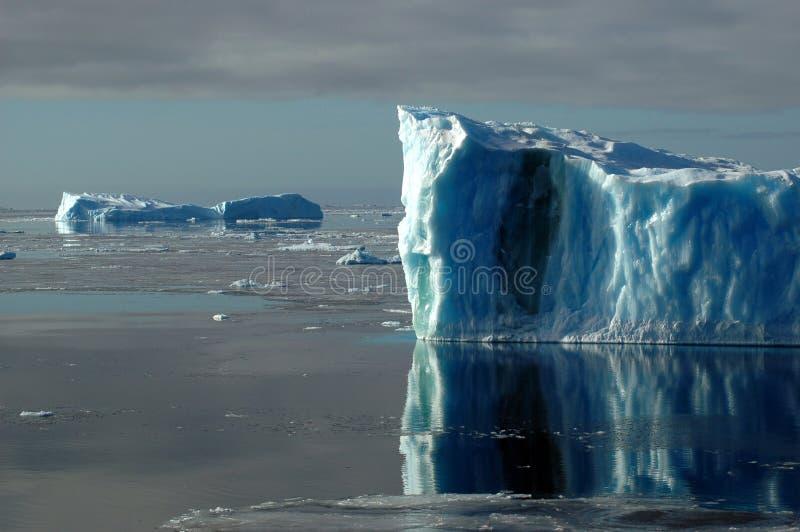 Two blue Antarctic icebergs stock photo