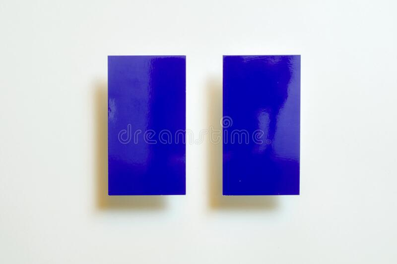 Two blue blank gloss linear textured business cards flying and isolated on white paper background, us standard size 3.5 x 2 inches. Real non professional royalty free stock photos