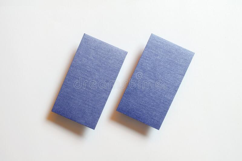 Two blue blank matt linear textured business cards flying and isolated on white paper background, us standard size 3.5 x 2 inches. Real non professional studio stock photos