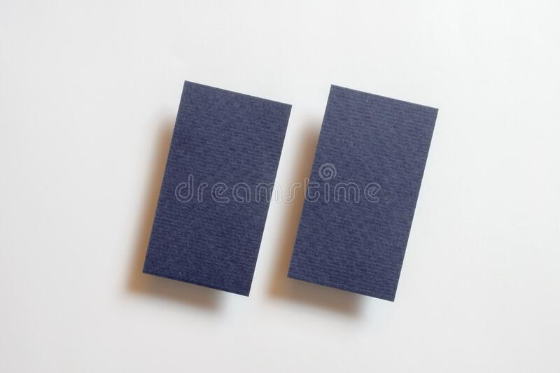 Two blue blank matt linear textured business cards flying and isolated on white paper background, us standard size 3.5 x 2 inches. Real non professional studio stock images