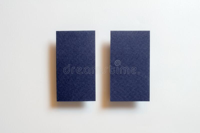 Two blue blank matt textured business cards flying and isolated on white paper background, us standard size 3.5 x 2 inches, real. Non professional studio photo stock photography