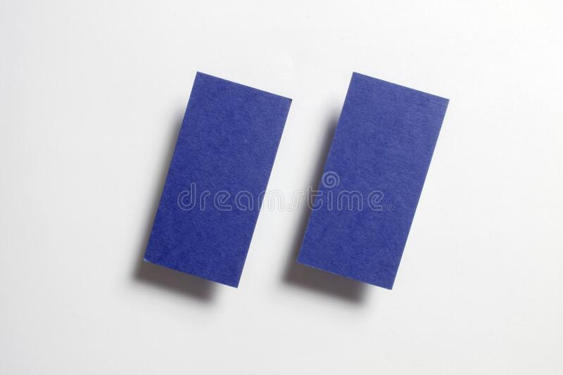 Two blue blank matt textured business cards flying and isolated on white paper background, us standard size 3.5 x 2 inches,. Studio photo royalty free stock photos