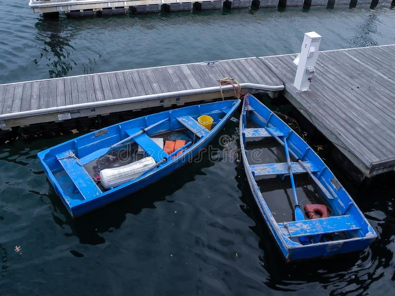 Two Old Blue Row Boats in the Water Tied to a Wooden Dock. Two Old Weathered Blue Row Boats in the Water Tied to a Wooden Dock royalty free stock photo