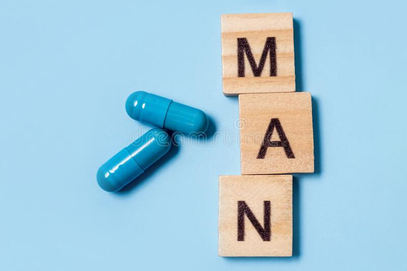 Two blue capsules and inscription man. Pills for men`s health and sexual energy. Concept of erection, potency. Treatment. Of male infertility and impotence stock photography