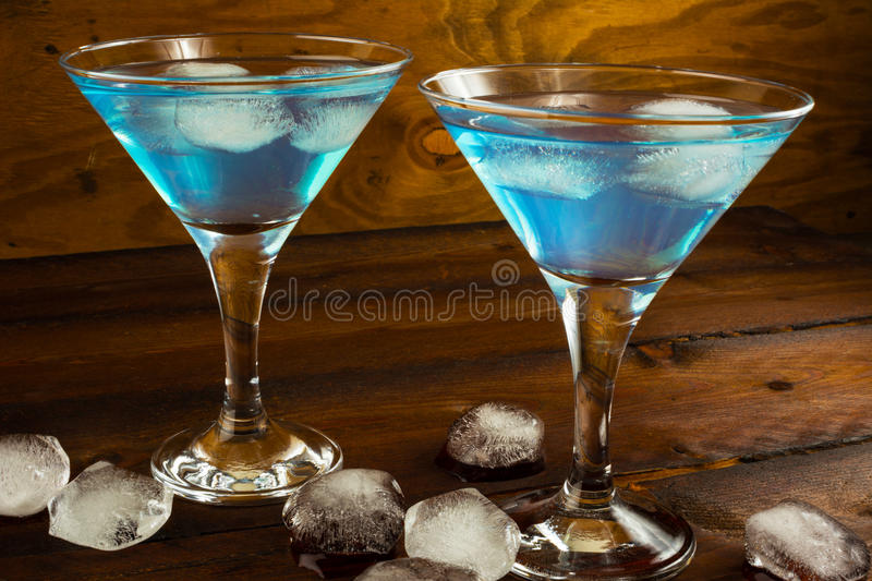 Two blue cocktails in glasses on dark wooden background royalty free stock image