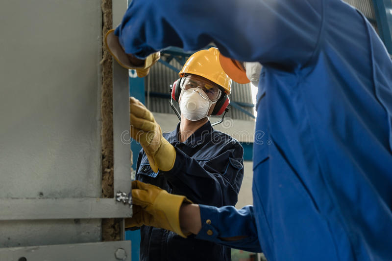 Two blue-collar workers wearing protective equipment stock photo