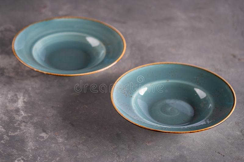 Two blue empty clay plates staying at table. Two blue empty clay plates staying at the table royalty free stock photography