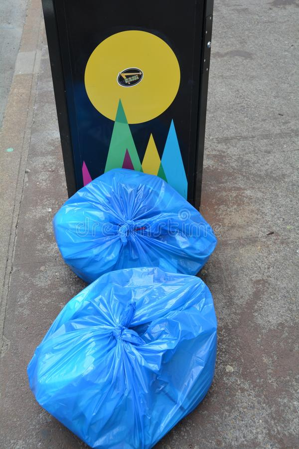 Two blue garbage bags in Portland, Oregon. These are two blue garbage bags stacked near a garbage can on a downtown Portland, Oregon street stock photos