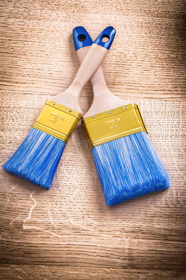Two blue paint brushes with wooden handles on. Vintage board wooden board construction concept royalty free stock images