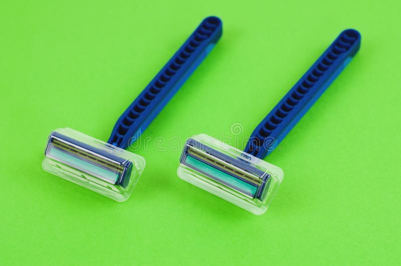 Two blue plastic disposable razors with two blades and humid strip in transparent cover on blank green paper royalty free stock images