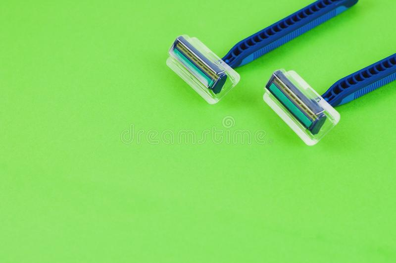 Two blue plastic disposable razors with two blades and humid strip in transparent cover on blank green paper royalty free stock image