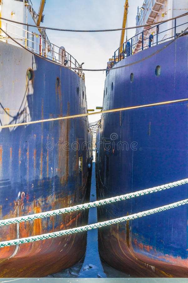 Two blue sea ships side to side in the port stock photo