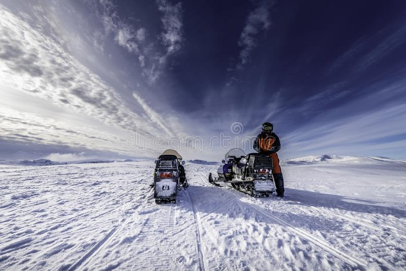 Two blue snowmobiles back side with a boy dressed for winter driving in cold mountains, he waits for his friend royalty free stock photos