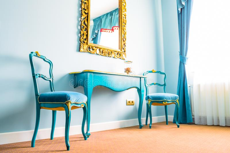 Two blue vintage chairs and a wooden table, next to a wall with a mirror, decorated with yellow floral swirls on its frame. stock images