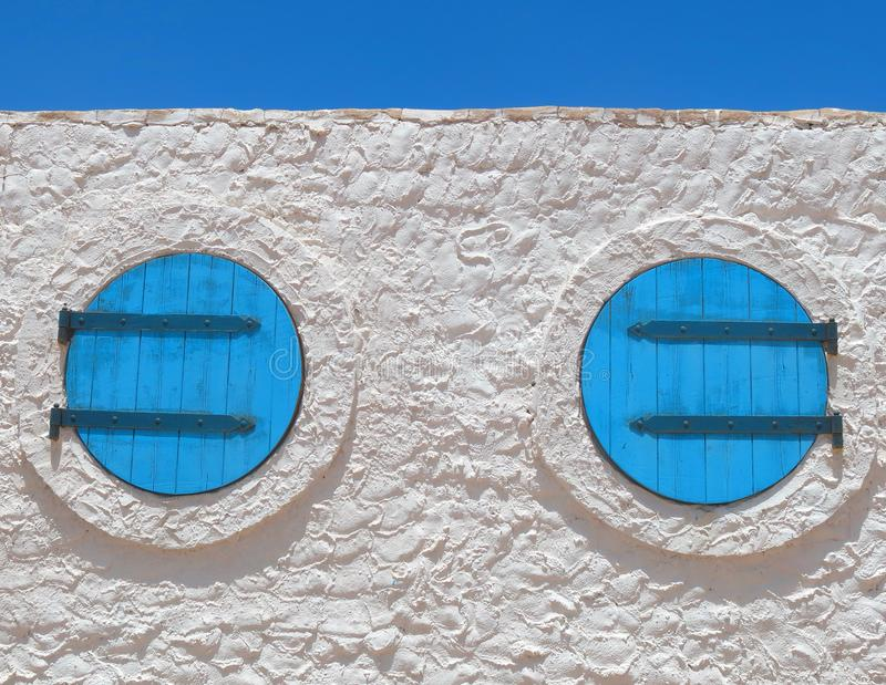 Two blue windows in the shape of a circle in the white house royalty free stock photography