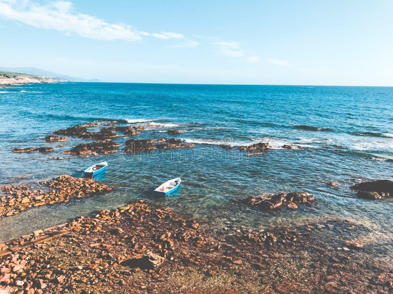 Two Blue Wooden Boats on Ocean Portrait stock photo