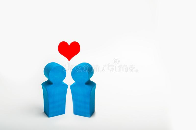 Two blue wooden figures of people stand on white background and heart over them. love. two persons of homosexual orientation. the. Concept of relations between royalty free stock photography