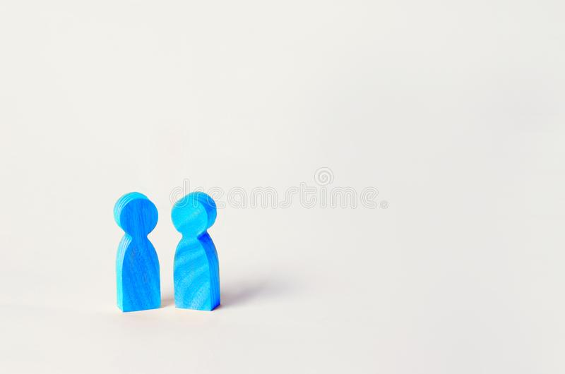 Two blue wooden figures of people stand on white background. two persons of homosexual orientation. the concept of relations betwe stock photography