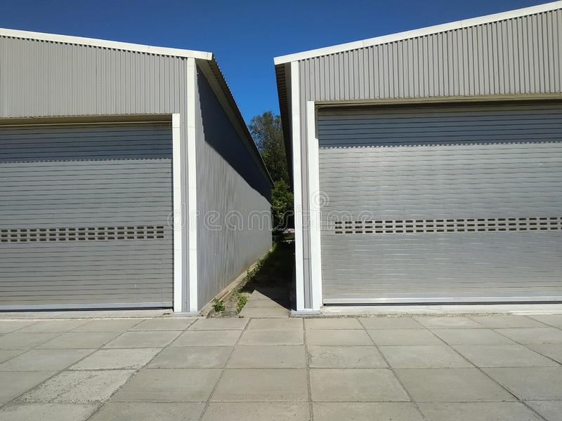 Two boarded metal hangar with closed rolling doors. Rolling shutter door of two large garages. Warehouse entrance with closed royalty free stock image