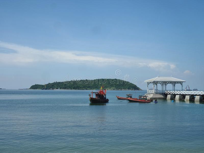 Two boatd and the long White outreach to the sea bridge on the remote island. Quiet beach in ceased palace area on Sichang Island , Chonburi , Thailand stock image