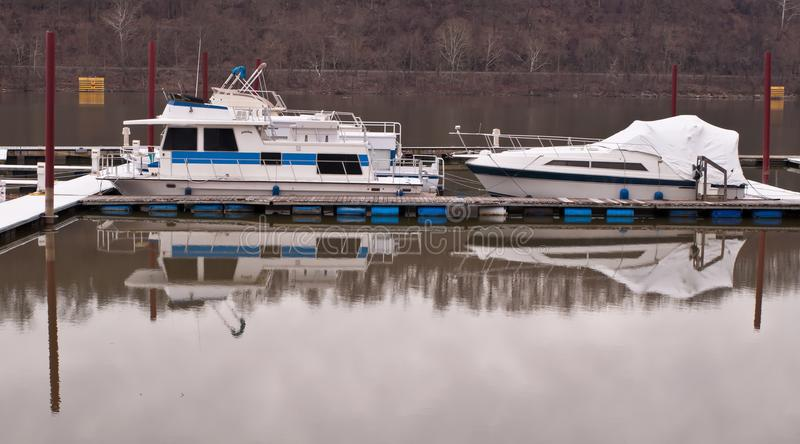 Two boats dry docked in a river stock images
