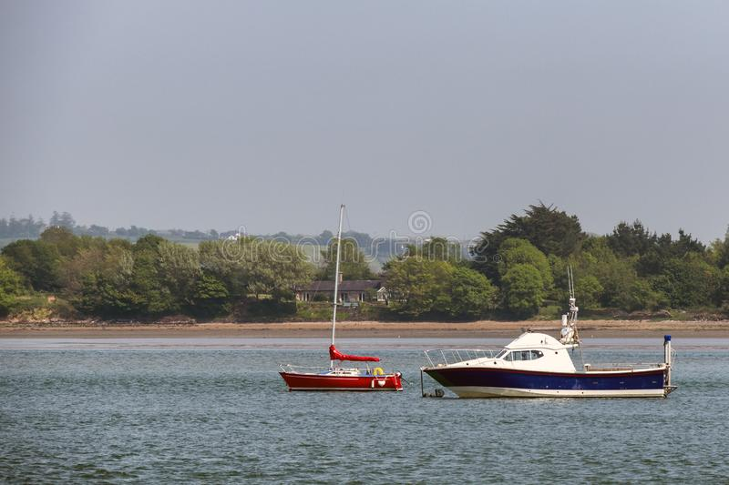 Some boats moored in an Irish bay with trees in background royalty free stock photo